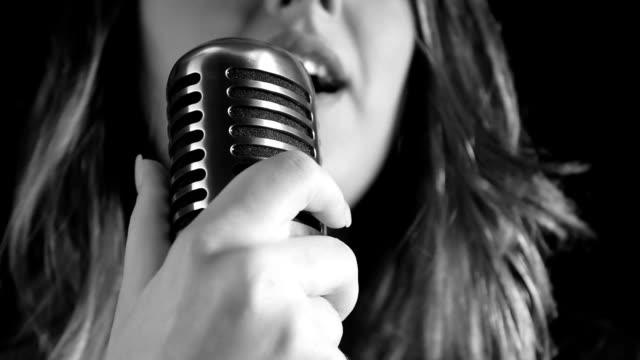 Beautiful woman singing to the microphone in a studio video