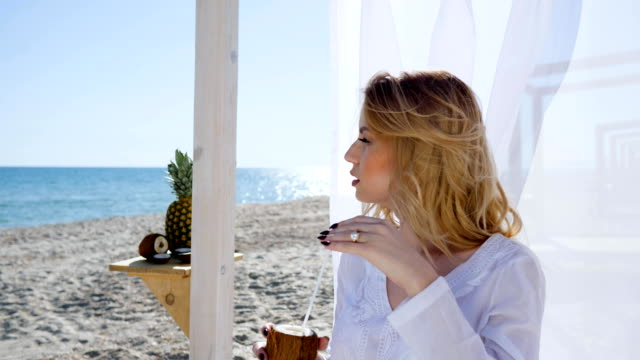 Beautiful woman sitting in bungalow with white curtains on shore, girl resting on beach, drinking coconut juice video