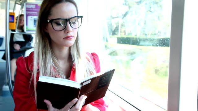 Beautiful woman sitting in tram reading  book video