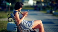 Beautiful woman sitting on the outdoor bench and typing on the phone video