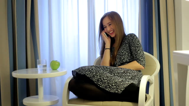 Beautiful woman smartphone in hotel room seating at table video