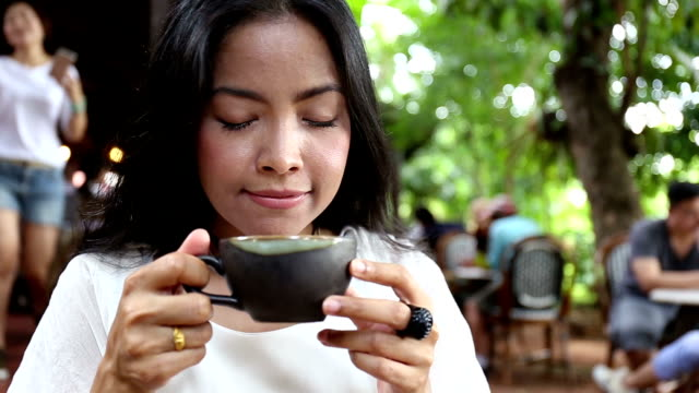 Beautiful woman smelling the aroma of her morning coffee in garden video