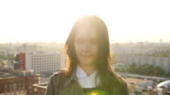 beautiful woman standing on the roof of high-rise building at sunset looking at the camera. Wind blows her hair Slow mo video