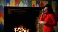 Beautiful woman stands by the fireplace and talking on the phone video