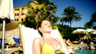 Beautiful woman sunbathing by the pool, dolly shot video