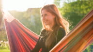 Beautiful woman swinging in a hammock and daydreaming video