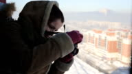 Beautiful woman takes photos of the winter city from a height video