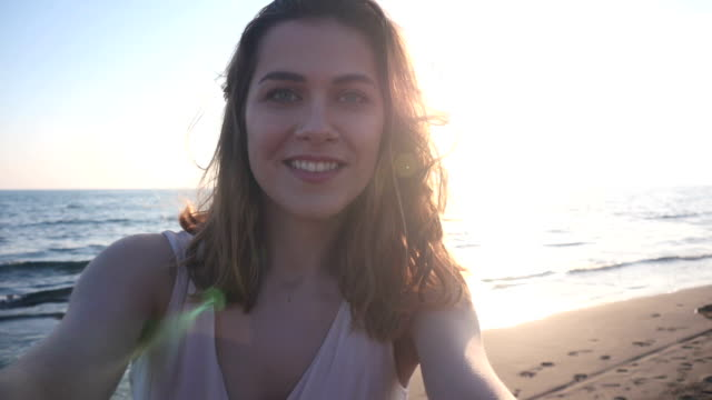 beautiful woman taking selfie using phone on beach at sunset smiling and spinning enjoying nature and lifestyle video
