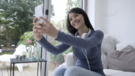 Beautiful woman taking selfies with her smartphone video