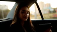 Beautiful woman tourist traveling in a taxi and rewritten with your friends on your phone video
