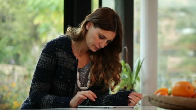 Beautiful woman using digital tablet at home. video