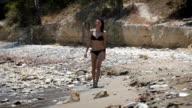 A beautiful woman walking at a beach wearing black bikini video