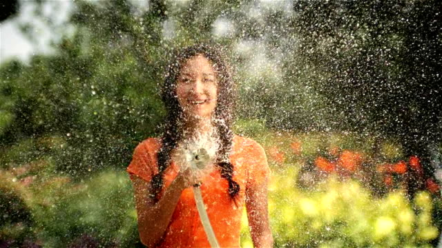 beautiful woman watering in garden video