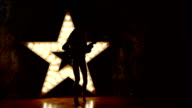 beautiful woman with electric guitar.sexy girl in leather, shining star in the background. slow motion, silhouette video