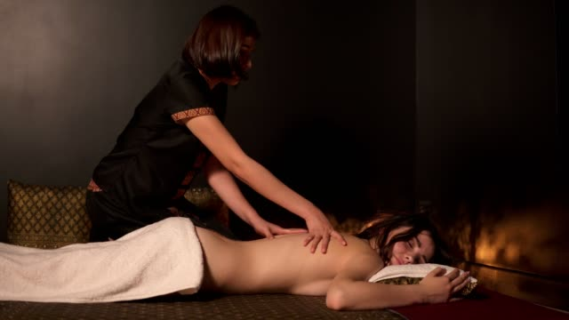 Beautiful woman with oiled skin having thai massage of her back and shoulders in spa by a female massagist in kimono. Shot in 4k video