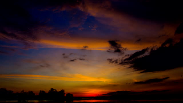Beautiful yellow sunset on reservoirs with orange sky and clouds, time lapse. video
