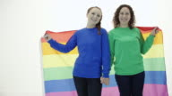 Beautiful young adult female couple blanketed by gay pride flag video