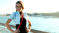 Beautiful young adult woman playing, flirting with camera near the sea video