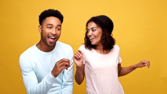 Beautiful young afro american couple dancing together isolated over yellow background video