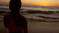 Beautiful young Asian woman gazing at sunset on sandy beach after running video