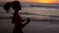 Beautiful young Asian woman running on sandy beach next to ocean waves video