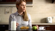Beautiful young attractive businesswoman drinking coffee. Having cornflakes for breakfast video