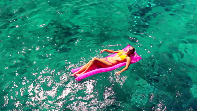 Beautiful Young Blonde Women In Bikini Floating on Pink Inflatable Raft in Crystal Ocean in Hawaii. video