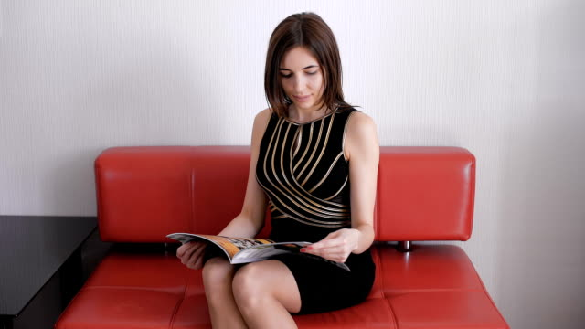 Beautiful young brown haired girl reading a magazine while sitting relaxing on a couch video