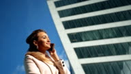 Beautiful young business woman calling by phone on the background of skyscrapers video
