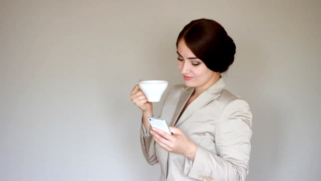 Beautiful young businesswoman, professional female employer typing text message on cellphone and drinks coffee video