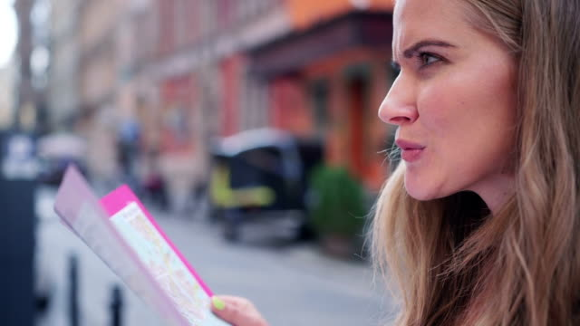 Beautiful young caucasian woman with a map during sightseeing in a city. video