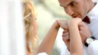 Beautiful young couple, groom kissing her hands at sunset video