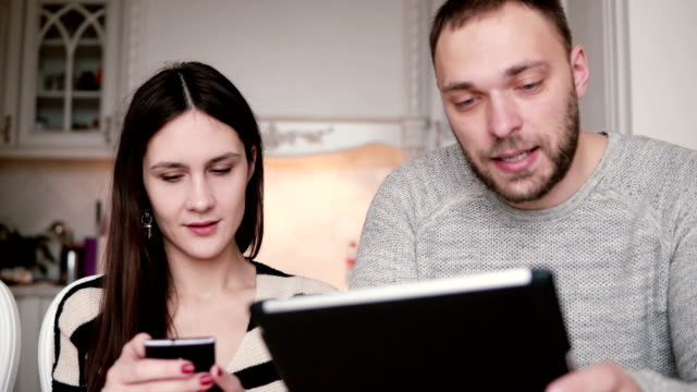 beautiful young couple man and woman using phone and tablet computer touchscreen in a bright dining video
