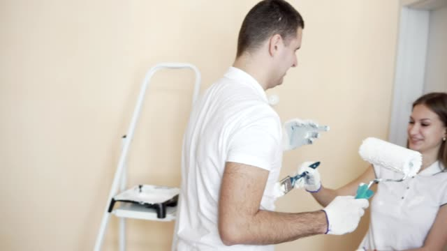 Beautiful young couple painting the walls and each other in a new apartment, laughing and having fun. Young family makes repairs in their new flat video