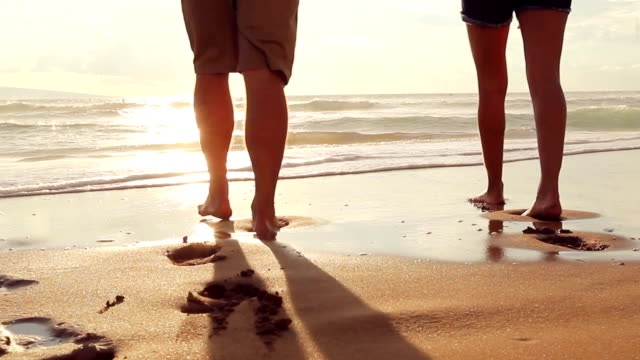 Beautiful Young Couple Walking on Beach Holding Hands at Sunset video