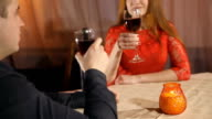 Beautiful young couple with glasses red wine in luxury restaurant video