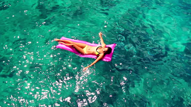 Beautiful Young Ethnic Pacific Islander Woman In Bikini Floating on Pink Inflatable Raft in Crystal Ocean in Hawaii. video
