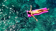 Beautiful Young Ethnic Pacific Islander Woman In Bikini Floating on Pink Inflatable Raft in Crystal Ocean in Hawaii. video