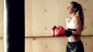Beautiful Young Female Athlete Exercising for Self Defense with Boxing Gloves and Body Bag. video