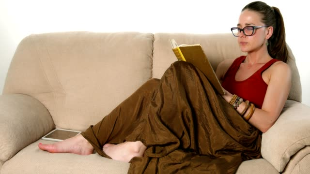 Beautiful young female lying comfortable on the couch and reading a book video