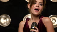 Beautiful young female vocalist singing into retro microphone video