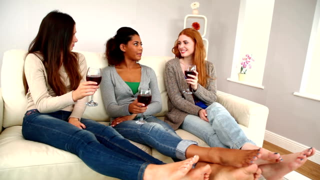 Beautiful young friends chatting while sitting on couch video