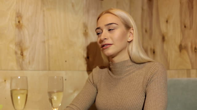 Beautiful young girl drinking champagne in cafe. video