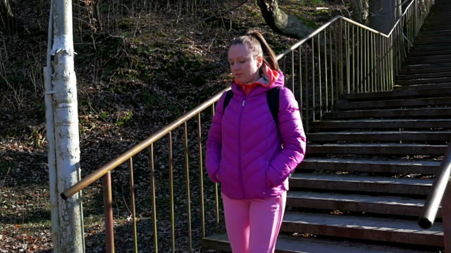 Beautiful young girl in forest go down stone steps Pink clothes, spring forest, Slow motion video