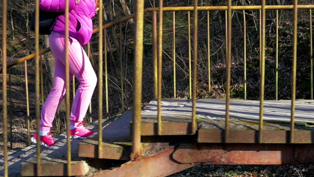 Beautiful young girl in forest go up stone steps Pink clothes, spring forest, Slow motion video