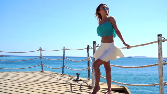 beautiful young girl in glasses standing on a pier near the sea and the wind is blowing in slow motion video