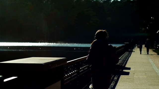 Beautiful young girl in park looking lake, evening. Pink clothes, springtime, Slow movement video