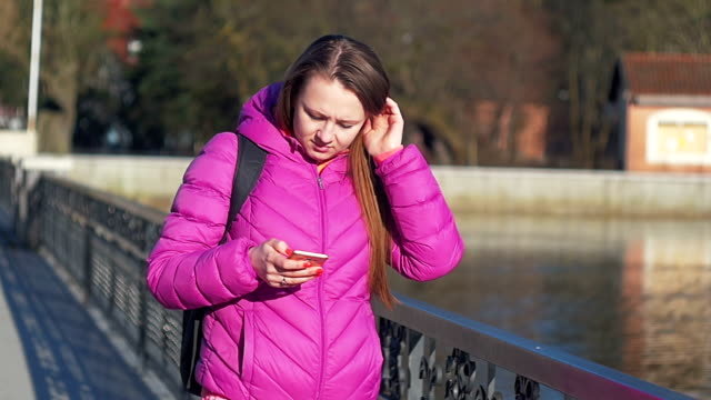 Beautiful young girl in park, on lake, reading message. Go to camera. Pink clothes, springtime, Slow motion. Close up shot video