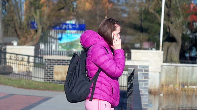 Beautiful young girl in park, on lake, talking on phone. Pink clothes, springtime, Slow motion, medium shot video