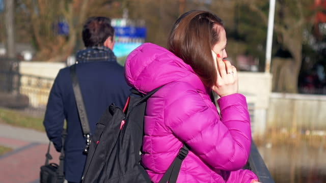 Beautiful young girl in park, on lake, talking on phone. Pink clothes, springtime Slow motion, close up shot video